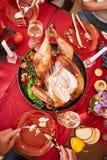Familie die traditionele Dankzegging Turkije op een feestelijke lijstachtergrond eten Geroosterd Turkije Het concept van de famil Royalty-vrije Stock Afbeelding