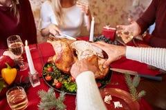 Familie die traditionele Dankzegging Turkije op een feestelijke lijstachtergrond eten Geroosterd Turkije Het concept van de famil Stock Afbeeldingen