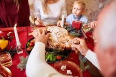 Familie die traditionele Dankzegging Turkije op een feestelijke lijstachtergrond eten Geroosterd Turkije Het concept van de famil Royalty-vrije Stock Foto's