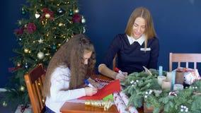 Familie die traditionele groetkaarten schrijven voor Kerstmis stock footage