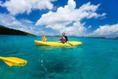 Familie, die in tropischem Ozean Kayak fährt Lizenzfreie Stockbilder