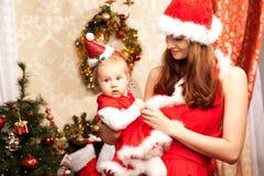 Familie, die um den Weihnachtsbaum sitzt Mutter und Baby im Ne lizenzfreies stockbild