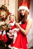 Familie, die um den Weihnachtsbaum sitzt Mutter und Baby im Ne lizenzfreie stockbilder