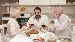 Familie, die um eine Tabelle sitzt, Spaß während des Familien-Abendessens isst, mitteilt und hat stock video footage