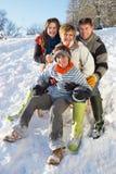 Familie, die unten Sledging Snowy Hügel genießt Stockfotografie