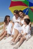 Familie, die unter buntem Regenschirm auf Strand lacht Stockfotos