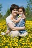 Familie, die unter Butterblumeen sitzt lizenzfreies stockfoto