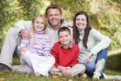Familie, die unter Herbstbäumen sitzt Stockbild