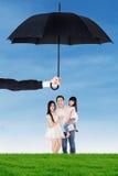 Familie, die unter Regenschirm am Feld steht Lizenzfreie Stockfotos