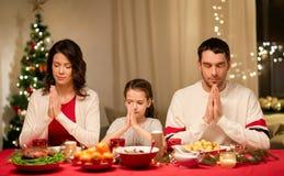 Familie die vóór maaltijd bij Kerstmisdiner bidden royalty-vrije stock afbeelding