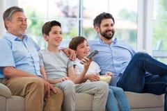 Familie die van drie generaties op TV letten Stock Foto's