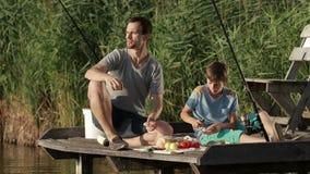 Familie die van maaltijd genieten door het meer terwijl visserij stock videobeelden