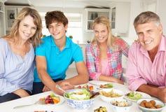 Familie die van maaltijd thuis geniet stock foto's