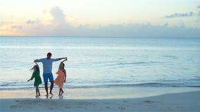 Familie die van papa en jonge geitjes strand van vakantie genieten Langzame Motie stock video