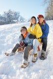 Familie die van Sledging onderaan SneeuwHeuvel geniet Royalty-vrije Stock Foto