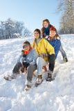 Familie die van Sledging onderaan SneeuwHeuvel geniet Royalty-vrije Stock Afbeelding
