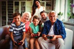 Familie die van videospelletje in woonkamer genieten stock afbeelding