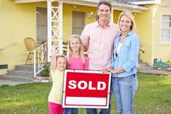 Familie, die Verkaufszeichen außerhalb des Hauses bereitsteht Lizenzfreies Stockbild