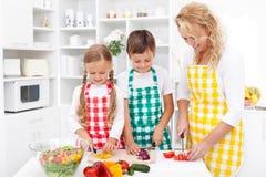 Familie die verse salade voorbereidt stock afbeelding