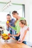 Familie die verse vruchten voor het gezonde leven in keuken eten Stock Foto