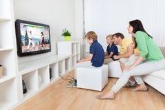 Familie, die Videospiel im Fernsehen spielt lizenzfreie stockfotos