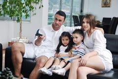 Familie die vlakke TV wathching bij modern huis binnen Stock Foto's