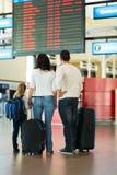 Familie die vluchtinformatie controleren Stock Foto
