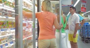 Familie die voedsel in de zuivelsectie van supermarkt nemen stock video