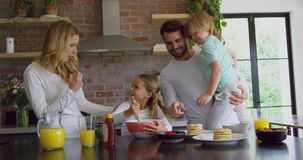 Familie die voedsel op worktop in keuken voorbereiden bij comfortabel huis 4k stock video