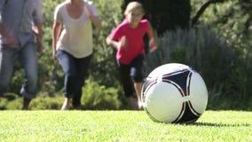 Familie die Voetbal in Tuin lopen te schoppen stock video