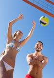Familie, die Volleyball am Seestrand spielt Lizenzfreies Stockbild