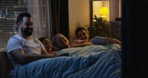 Familie, die vom Bett fernsieht stock footage