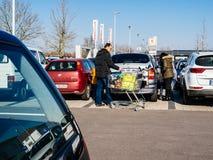 Familie die voor voedsel in Kaufland-supermarktparkeren winkelen stock fotografie