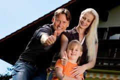 Familie, die vor ihrem Haus sitzt Stockbilder