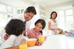 Familie, die vor Vater Leaves For Work frühstückt Lizenzfreie Stockfotografie