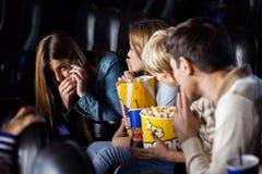 Familie die Vrouw bekijken die Mobilofoon binnen met behulp van Royalty-vrije Stock Foto
