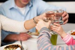 Familie, die Wassergläser in der Feier röstet Stockbilder