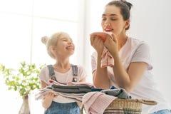 Familie die wasserij thuis doen stock foto's