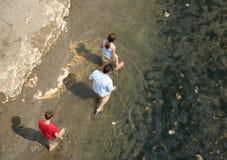 Familie die in water loopt stock afbeelding