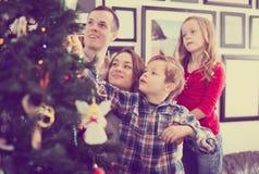 Familie, die Weihnachtsbaum verziert Lizenzfreie Stockfotografie