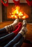 Familie die wollen sokken dragen die in chalet door firepla zitten te branden royalty-vrije stock fotografie