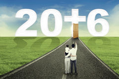 Familie, die Zahlen 2016 und ein Kreuz schaut Stockbild