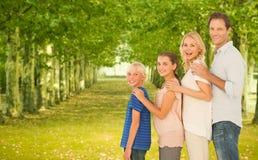 Familie die zich achter elkaar tegen rijbomen bevinden op achtergrond royalty-vrije stock fotografie