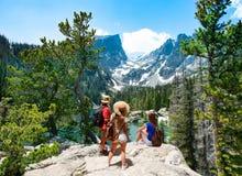 Familie die zich bovenop de berg bevinden die van mooi landschap genieten royalty-vrije stock foto's