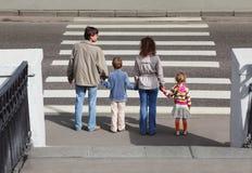 Familie die zich dichtbij oversteekplaats bevindt, erachter Stock Foto