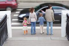 Familie die zich dichtbij voetgangersoversteekplaats bevindt Stock Fotografie