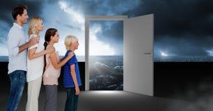 Familie die zich door open deur met donkere overzeese gloed en surreal hemel bevinden royalty-vrije stock foto's