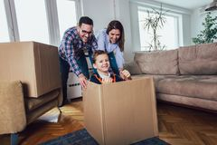 Familie die zich naar huis met rond dozen beweegt, en pret heeft stock fotografie