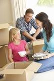 Familie die zich in Nieuw die Huis bewegen door Dozen wordt omringd In te pakken royalty-vrije stock afbeelding