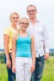 Familie die zich op gras van gazon of gebied bevinden stock foto's